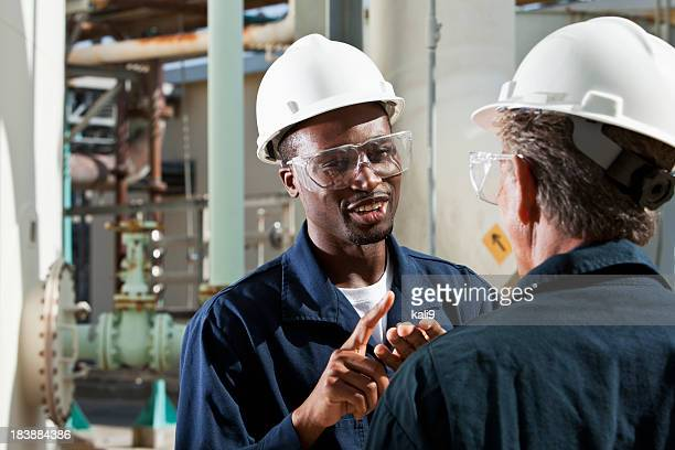 multiracial workers at industrial plant talking - black jumpsuit stock photos and pictures