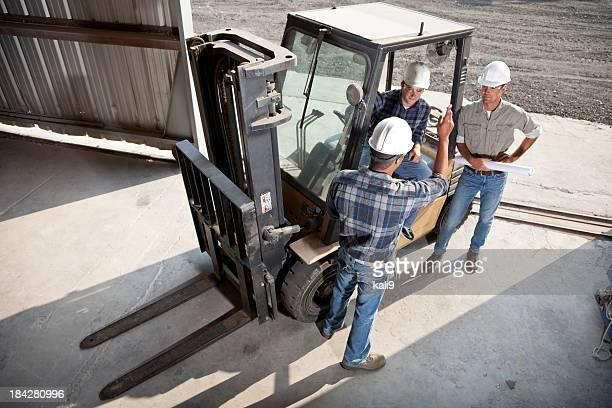 Multirracial trabalhadores com máquina elevadora de cargas