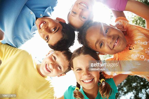 Multiracial young friends making a huddle against sky