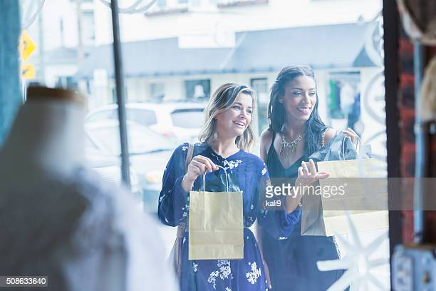 Multi-racial young women window shopping