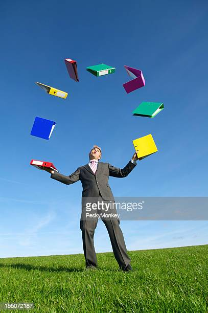 Multitasking Businessman Juggling File Folder Binders in Empty Meadow