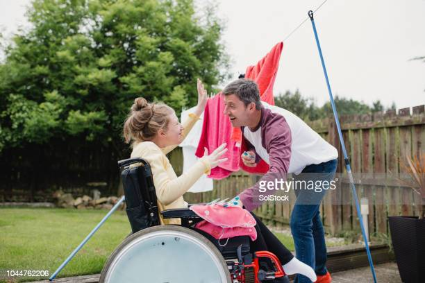 multitasking dad with happy disabled daughter - epilepsy stock pictures, royalty-free photos & images