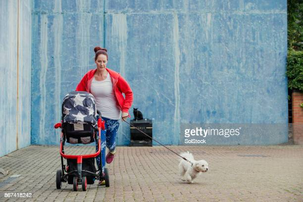 multitasking jogging mother - three wheeled pushchair stock pictures, royalty-free photos & images