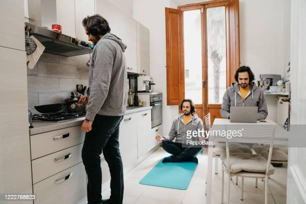 uomo multitasking che fa molte attività quando è in quarantena - ripetizione foto e immagini stock