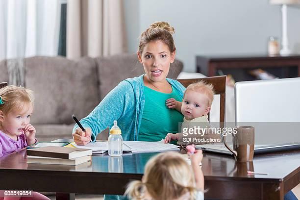 Multi-tasking mom studies and cares for children