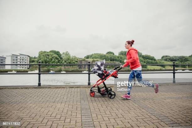 multitasking mother running with pushcair - three wheeled pushchair stock pictures, royalty-free photos & images