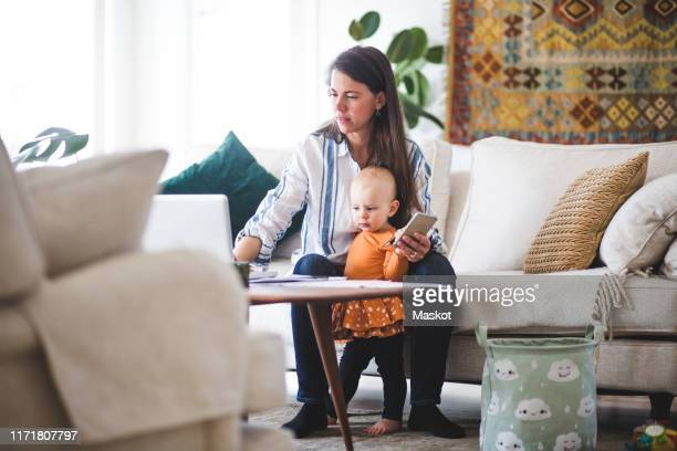 multi-tasking mother using laptop while taking care of daughter in living room - homemaker stock pictures, royalty-free photos & images