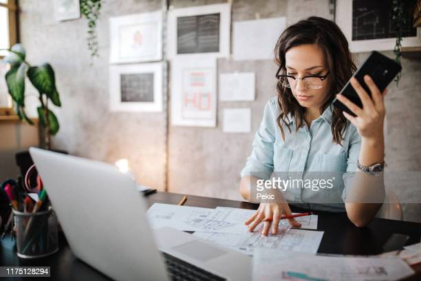 multitasking of young female entrepreneur at work - entrepreneur stock pictures, royalty-free photos & images