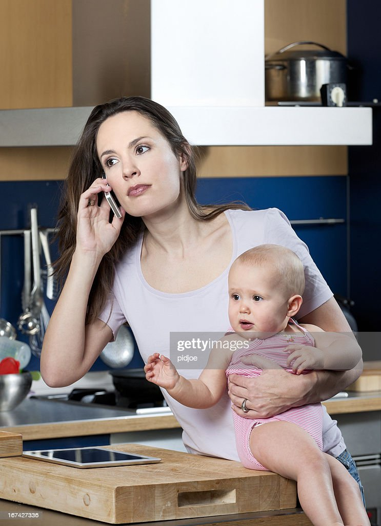 multi-tasking woman on the phone holding baby girl in kitchen : Stock Photo
