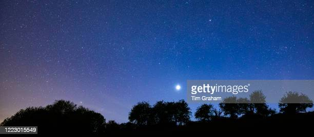 Multitude of stars and a shooting star in night sky with Venus at its brightest stage this year in prominent view over southern England, United...