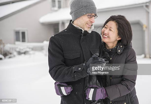 Multy-ethnic couple have fun outdoor under the snowfall