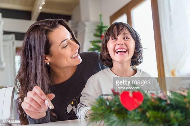 mum and child decorating Christmas wreath