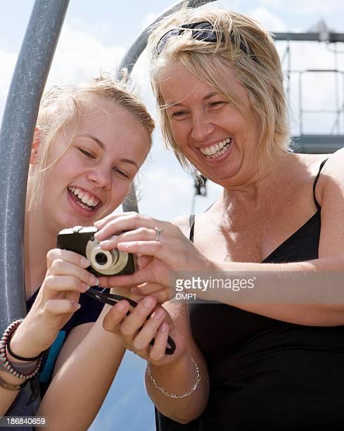 Mère et fille à l'extérieur en riant dans l'appareil photo