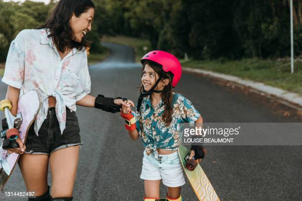 mum and daughter skateboarding together - showus stock pictures, royalty-free photos & images
