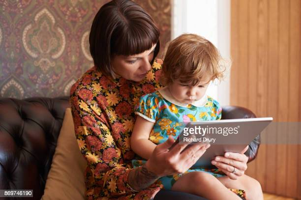 Mum and daughter using digital tablet in their living room