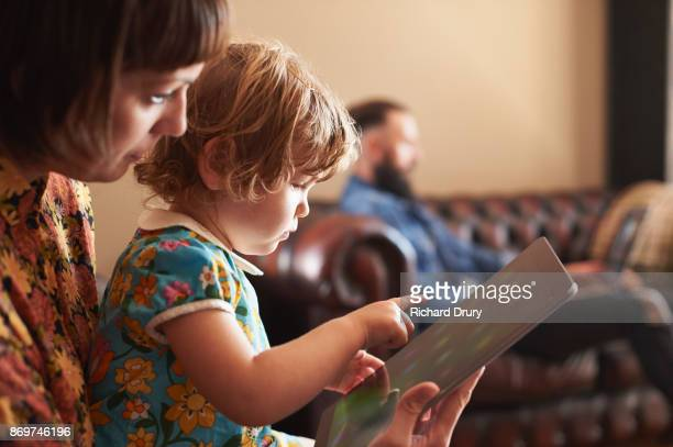 mum and daughter using digital tablet in their living room - responsibility stock pictures, royalty-free photos & images