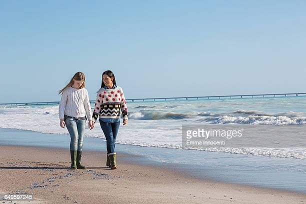 mum and daughter walking on beach by the hand