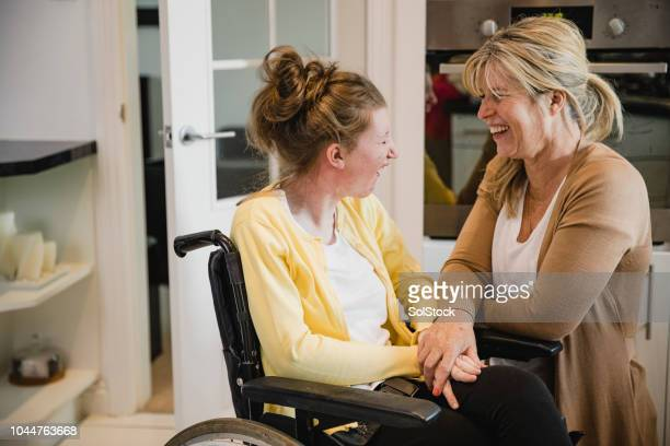 mum and disabled daughter in kitchen - adult stock pictures, royalty-free photos & images