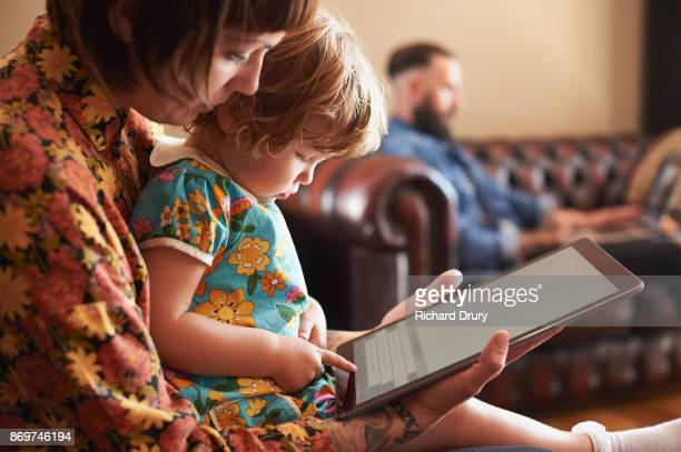 Mum and toddler girl using digital tablet in their living room