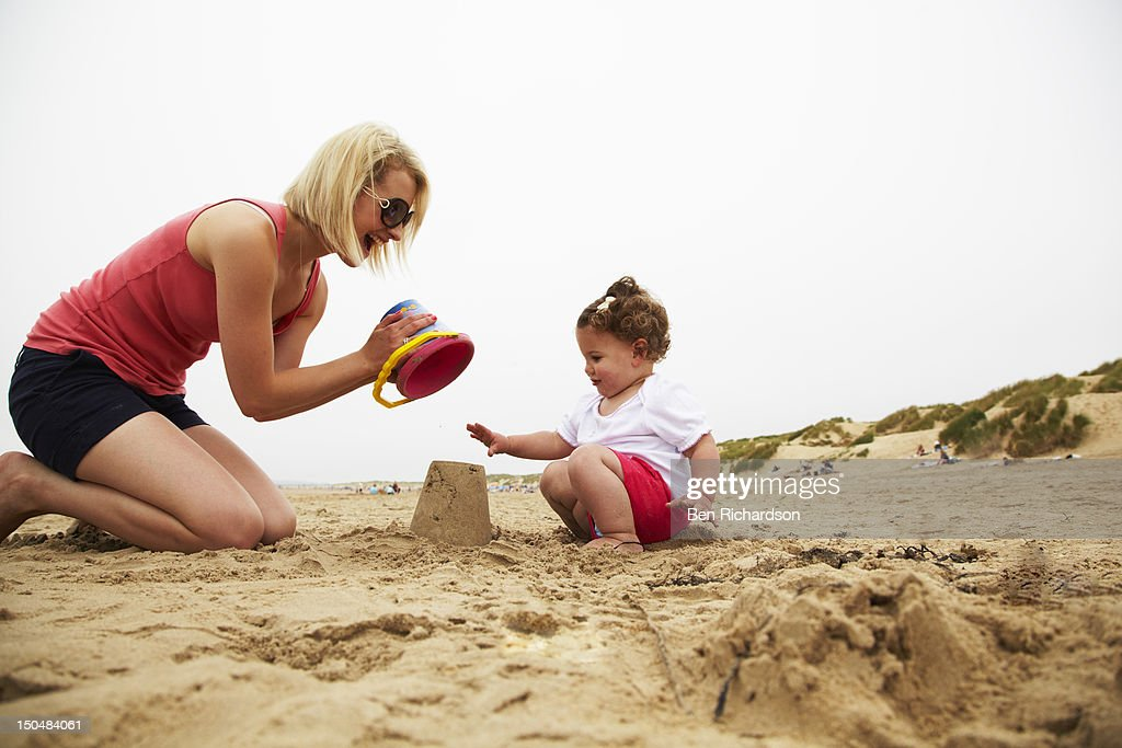 Mum and toddler making sandcastles on beach : Stock Photo