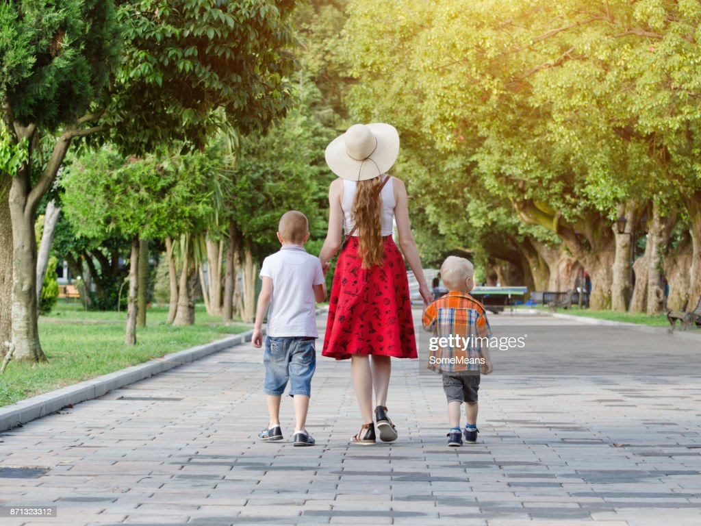 Mum and two sons walking in the park, sunny day. View from the back : Stock Photo