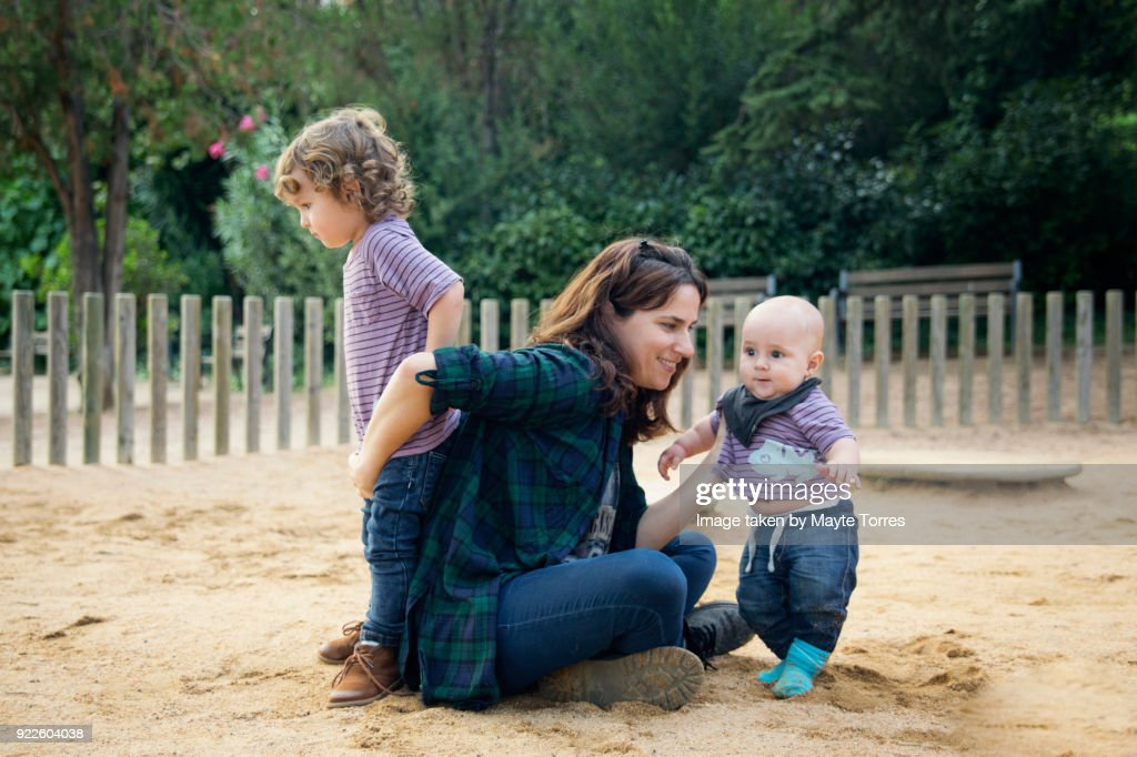 mum busy playing with babies at the playground : Stock Photo