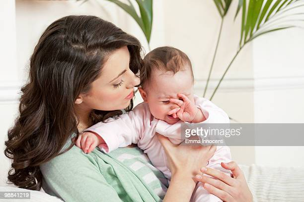 mum consoling crying child - newhealth stock pictures, royalty-free photos & images