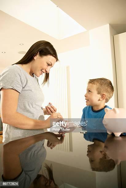 mum handing boy money
