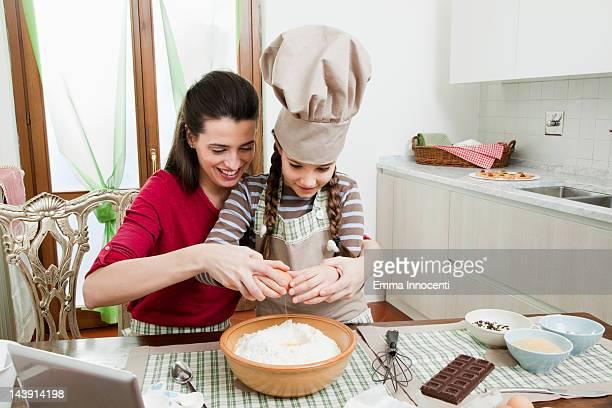 mum helping daughter baking cake
