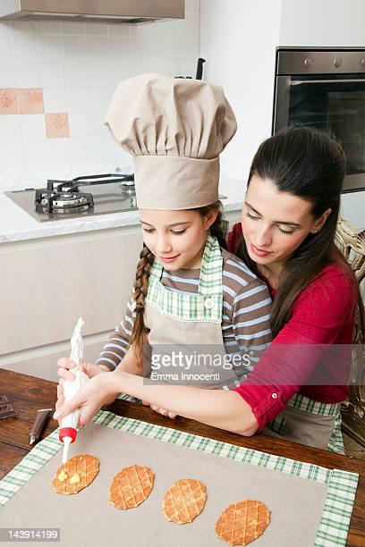 mum helping daughter decorating cookies