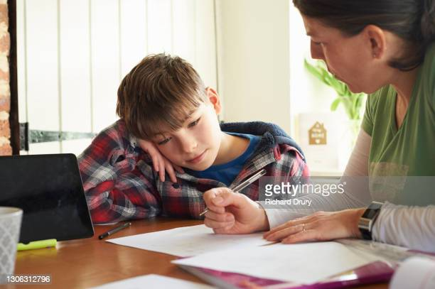 mum helping her young son to do his homework at the kitchen table - richard drury stock pictures, royalty-free photos & images
