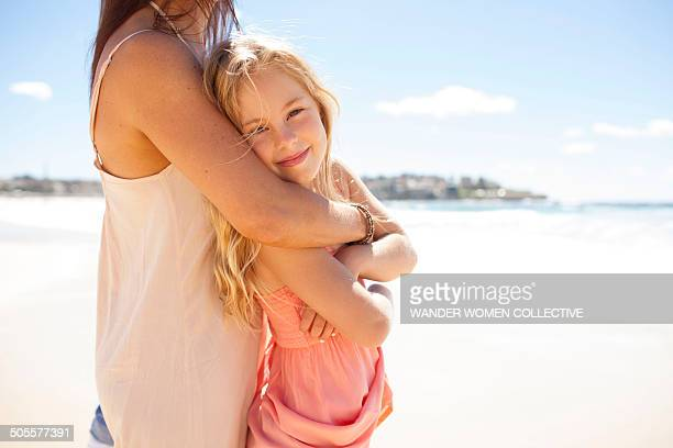 Mum holding daughter under arms on Bondi Beach