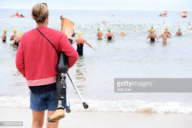 A mum holds her sons artificial leg while he competes during the 2020 Australian Open Water Swimming Championships at Brighton Beach on January 26...