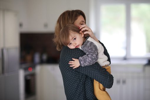 A mum hugging her 1 year old baby boy in the kitchen - gettyimageskorea