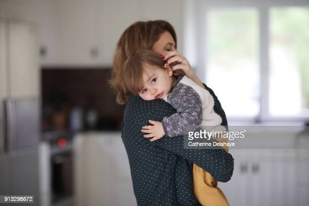 A mum hugging her 1 year old baby boy in the kitchen