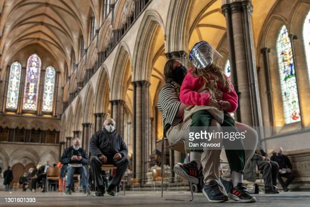 Mum Jade, waits with her daughter Lola after receiving her Covid-19 jab at a vaccination centre at Salisbury Cathedral on February 11, 2021 in...