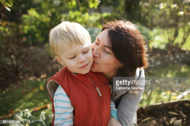 a mum kissing her 3 years old son in the garden - 35 39 years ストックフォトと画像