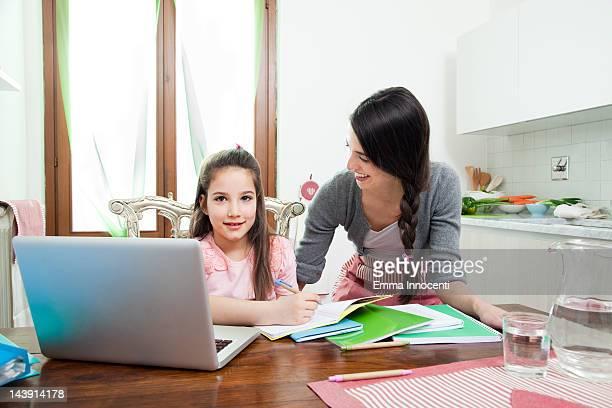 mum looking at daughter, laptop, homework, kitchen
