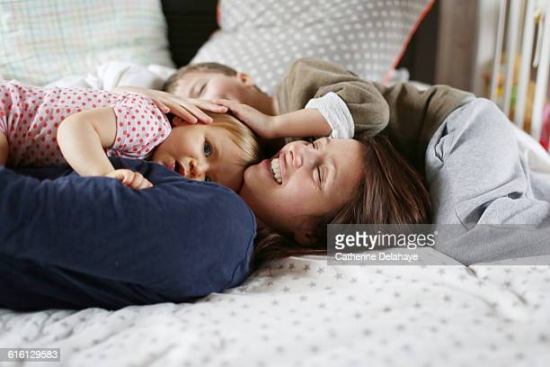a mum playing with her children on a bed - serene people stock pictures, royalty-free photos & images
