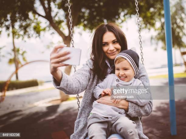 ママとブランコに乗る彼女の息子、selfie を取って