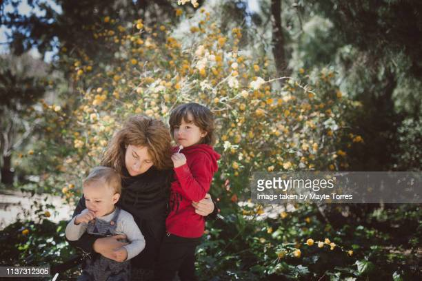 mum with boys in front of flowers - autism awareness stock pictures, royalty-free photos & images