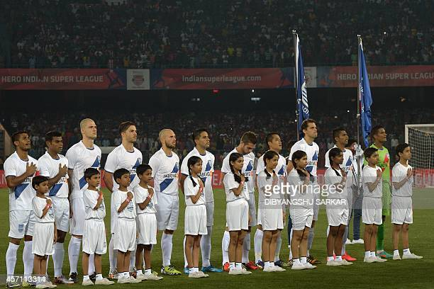 Mumbai City FC footballers observe the Indian national anthem prior to the Indian Super League football match between Atletico de Kolkata and Mumbai...