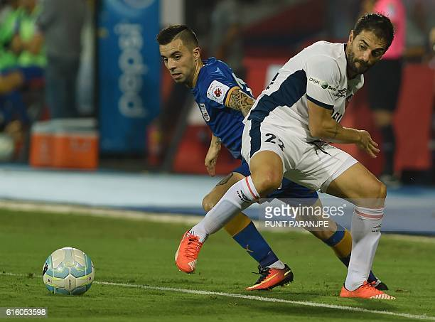 Mumbai City FC player Matias Defederico and FC Goa player Joffre Gonzalez tussle for the ball during the Indian Super League football match between...