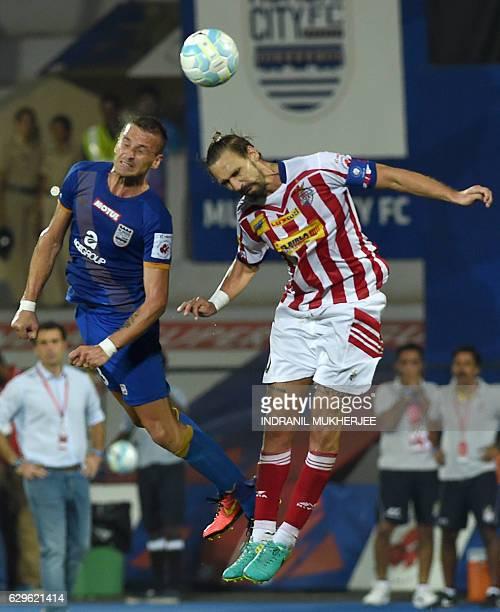 Mumbai FC's defender Lucian Goian and Atletico de Kolkata's midfielder Borja Fernandez jump in air to head the Indian Super League second leg...