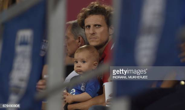 Mumbai FC's forward Diego Forlan looks on as he sits in the stands with his son during the Indian Super League second leg semifinal football match...