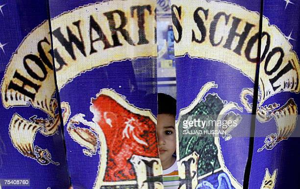 A young Indian child peers through a curtain at a replica of 'Hogwarts School' at a bookshop in Mumbai 14 July 2007 part of a promotional campaign...
