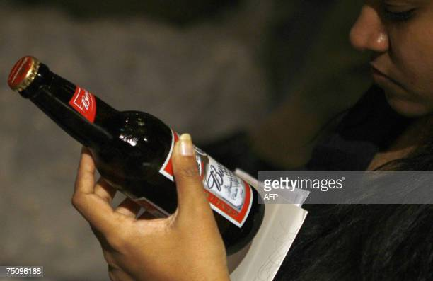 An Indian journalist inspects a bottle of Budweiser beer at a launch ceremony in Mumbai, 06 July 2007. Crown Beers India Ltd., the joint venture...