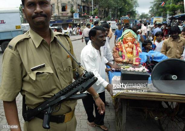 An Indian policemen watches over devotees as they carry home an idol of the elephant headed Hindu God Lord Ganesha through the streets of Mumbai 27...
