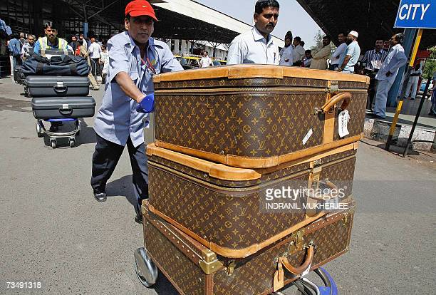 Indian luggage porters push trolleys laden with suitcases of unseen British model and actress Elizabeth Hurley and her husband Indian businessman...