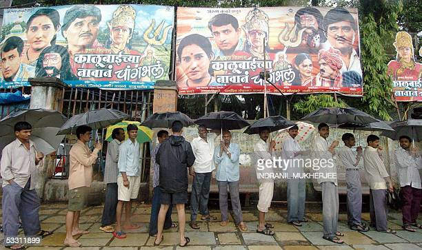 Indian movie buffs queue up in the rain outside a cinema theatre in Mumbai 01 August 2005 Monsoon rains that have pounded Mumbai for the past week...